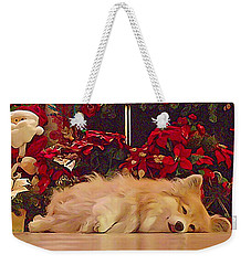 Weekender Tote Bag featuring the photograph Sleepy Holiday Corgi Surrounded By Poinsettias. by Kathy Kelly