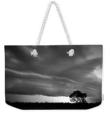 Weekender Tote Bag featuring the photograph Storm Passing Over Solitary Tree In The Desert by Keiran Lusk