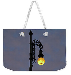 Weekender Tote Bag featuring the photograph Street Lamp Shining At Dusk by Michal Boubin
