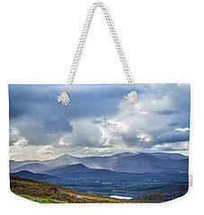 Weekender Tote Bag featuring the photograph Sun Rays Piercing Through The Clouds Touching The Irish Landscap by Semmick Photo