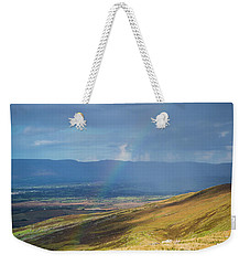 Weekender Tote Bag featuring the photograph Sunshine And Raining Down With Rainbow On The Countryside In Ire by Semmick Photo