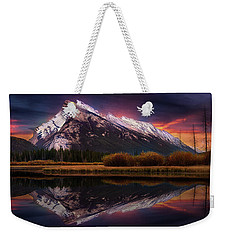 Weekender Tote Bag featuring the photograph The Sun Also Rises by John Poon