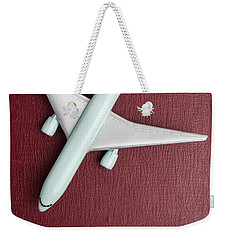 Weekender Tote Bag featuring the photograph Toy Airplane Over Red Book Cover by Edward Fielding