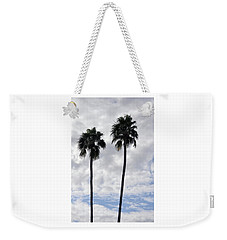 Twin Palm Trees Silhouetted Against Cloudy Blue Sky Weekender Tote Bag