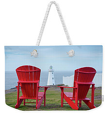 Weekender Tote Bag featuring the photograph Two Red Adirondack Chairs Looking Out To A Lighthouse by Art Whitton