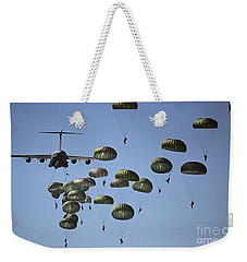 Weekender Tote Bag featuring the photograph U.s. Army Paratroopers Jumping by Stocktrek Images