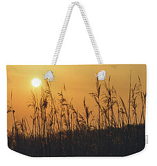 Weekender Tote Bag featuring the photograph View Of Sun Setting Behind Long Grass A by Jacek Wojnarowski