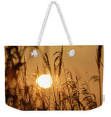 Weekender Tote Bag featuring the photograph View Of Sun Setting Behind Long Grass B by Jacek Wojnarowski