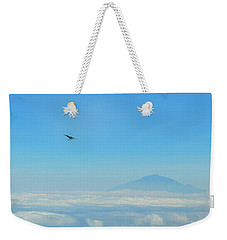 Weekender Tote Bag featuring the photograph White-necked Raven With Twig Soaring Over Mount Meru by Jeff at JSJ Photography