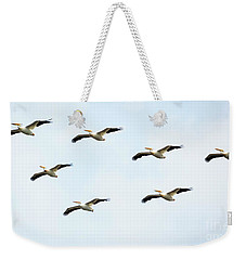 Weekender Tote Bag featuring the photograph White Pelican Flyby by Ricky L Jones