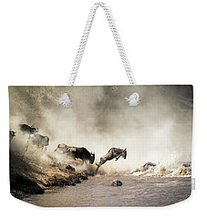 Wildebeest Leaping In Mid-air Over Mara River Weekender Tote Bag
