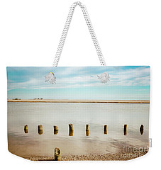 Weekender Tote Bag featuring the photograph Wood Pilings In Shallow Waters by Colleen Kammerer