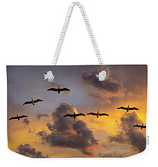 Weekender Tote Bag featuring the photograph Pelicans In The Clouds by John Rodrigues