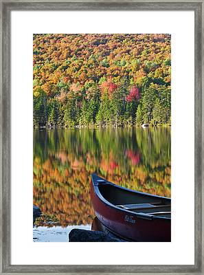 A Canoe On The Shoreline Of Pond Framed Print by Jerry and Marcy Monkman