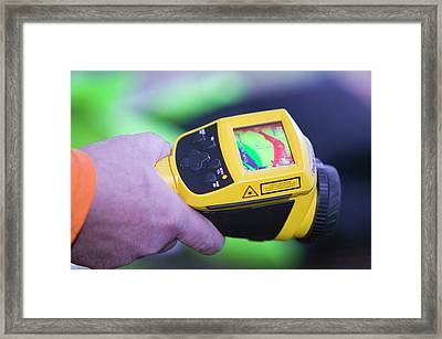 A Man Uses A Thermal Imaging Camera Framed Print
