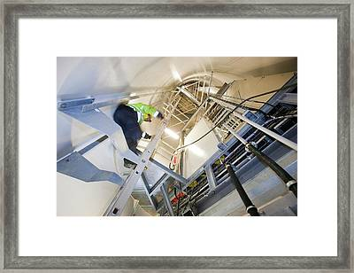 An Engineer Climbs A Wind Turbine Framed Print by Ashley Cooper