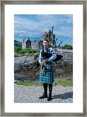 Bagpipe Player At Famous Eilean Donan Castle In The Highlands Of Scotland Framed Print by Frank Gaertner