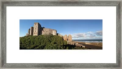 Bamburgh Castle Ruins Against A Blue Framed Print by John Short