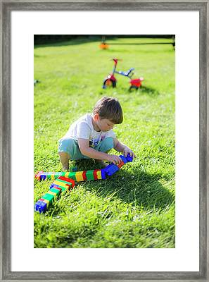 Boy Playing With Plastic Bricks Framed Print