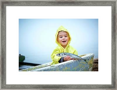 Boy Wearing Raincoat Holding A Mackerel Framed Print