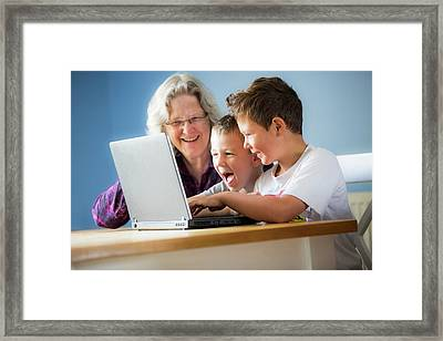 Boys Using Laptop With Grandmother Framed Print by Samuel Ashfield