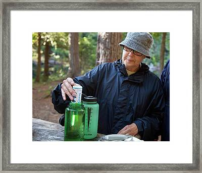 Camper Using A Uv Water Purifier Framed Print by Jim West