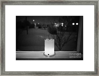 candle in the window looking out over snow covered scene in small rural village of Forget Saskatchew Framed Print by Joe Fox