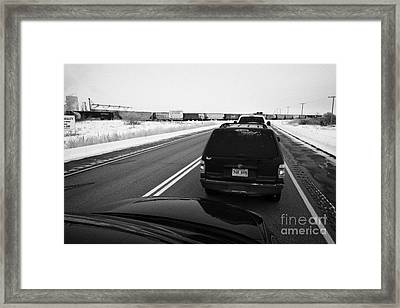 cars waiting on train crossing trans-canada highway in winter outside Yorkton Saskatchewan Canada Framed Print