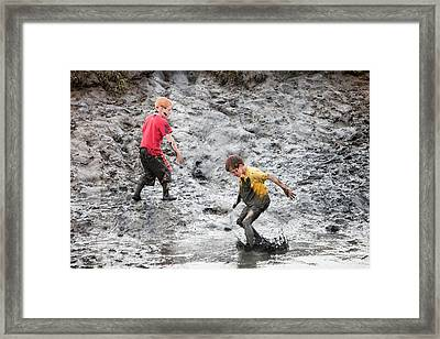 Children Playing In A Muddy Creek Framed Print by Ashley Cooper