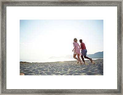 Couple Running On The Beach Framed Print