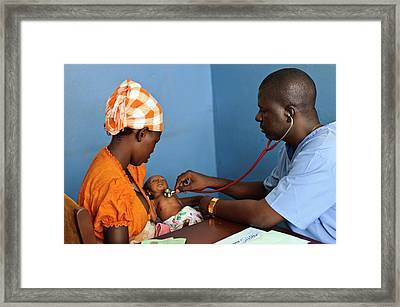 Doctor Examining A Baby Framed Print by Matthew Oldfield