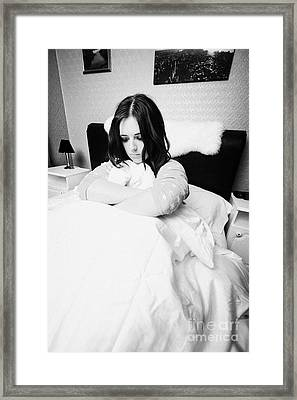 Early Twenties Woman Holding Duvet Tightly In Bed In A Bedroom Framed Print