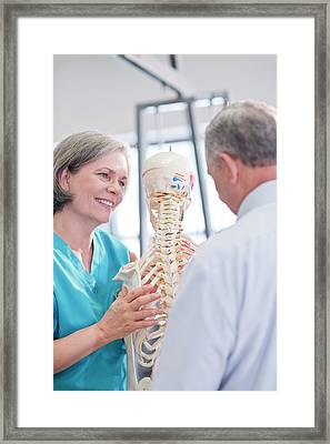 Female Chiropractor Showing Anatomical Model Framed Print by Science Photo Library