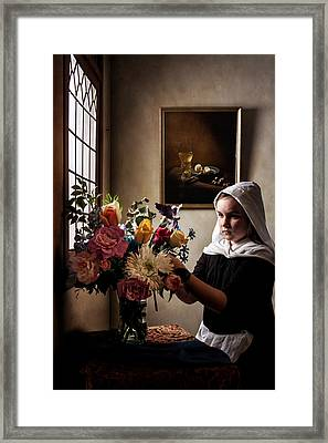 Girl Arranging A Flower Bouquet In A Glass Vase Framed Print by Levin Rodriguez
