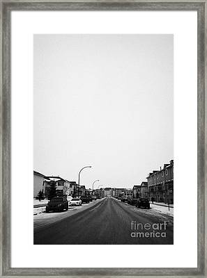 gritted salted cleared road in a residential housing suburbian development Saskatoon Saskatchewan Ca Framed Print by Joe Fox