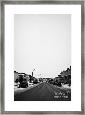 gritted salted cleared road in a residential housing suburbian development Saskatoon Saskatchewan Ca Framed Print by Joe Fox