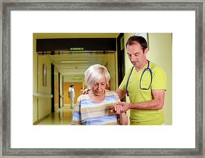 Hospital Doctor Assisting Elderly Woman Framed Print by Aj Photo
