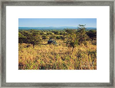 Jeep With Tourists On Safari In Serengeti. Tanzania. Africa. Framed Print by Michal Bednarek