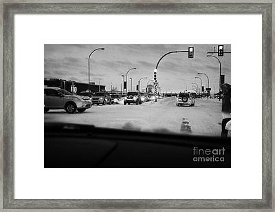 looking through car windshield at snow covered city intersection Saskatoon Saskatchewan Canada Framed Print by Joe Fox