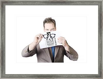Mature Man Holding Glasses And Eye Checking Chart Framed Print