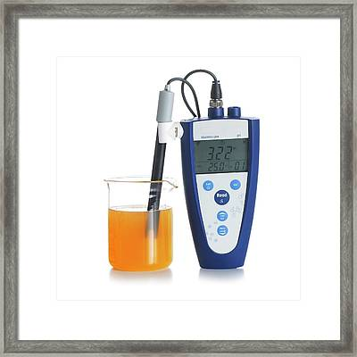 Ph Meter In Orange Juice Framed Print by Science Photo Library