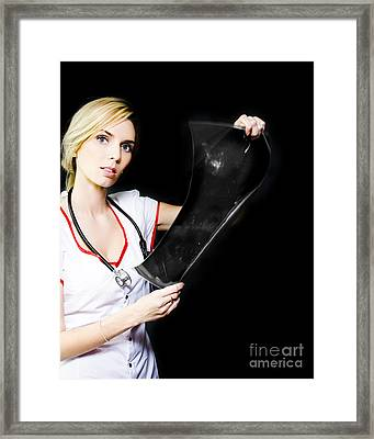 Pretty Young Nurse Studying An Xray Framed Print by Jorgo Photography - Wall Art Gallery