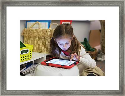 Primary School Girl Using Tablet Framed Print by Jim West