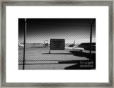 security chain link fencing with warning restricted area sign on the perimeter of mccarran airport L Framed Print by Joe Fox