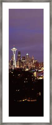 Skyscrapers In A City Lit Up At Night Framed Print