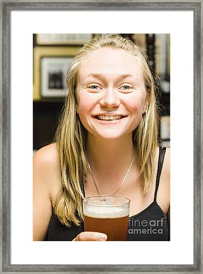 Smiling Blond Woman Drinking Pint Of Beer At Bar Framed Print
