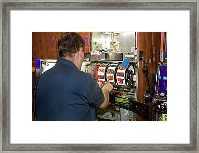 Technician Servicing A Slot Machine Framed Print by Jim West