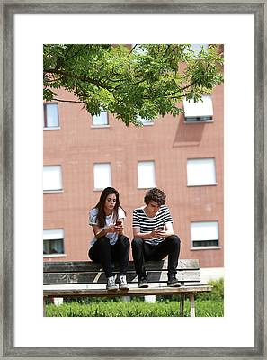 Teenage Couple Using Smart Phones Framed Print by Mauro Fermariello