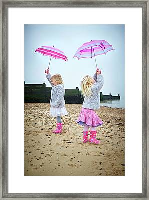 Two Girls On Beach Holding Umbrellas Framed Print by Ruth Jenkinson
