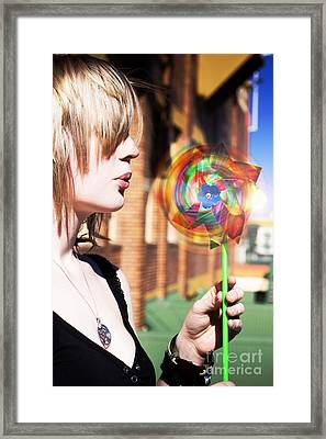 Woman Blowing Windmill Toy Framed Print by Jorgo Photography - Wall Art Gallery